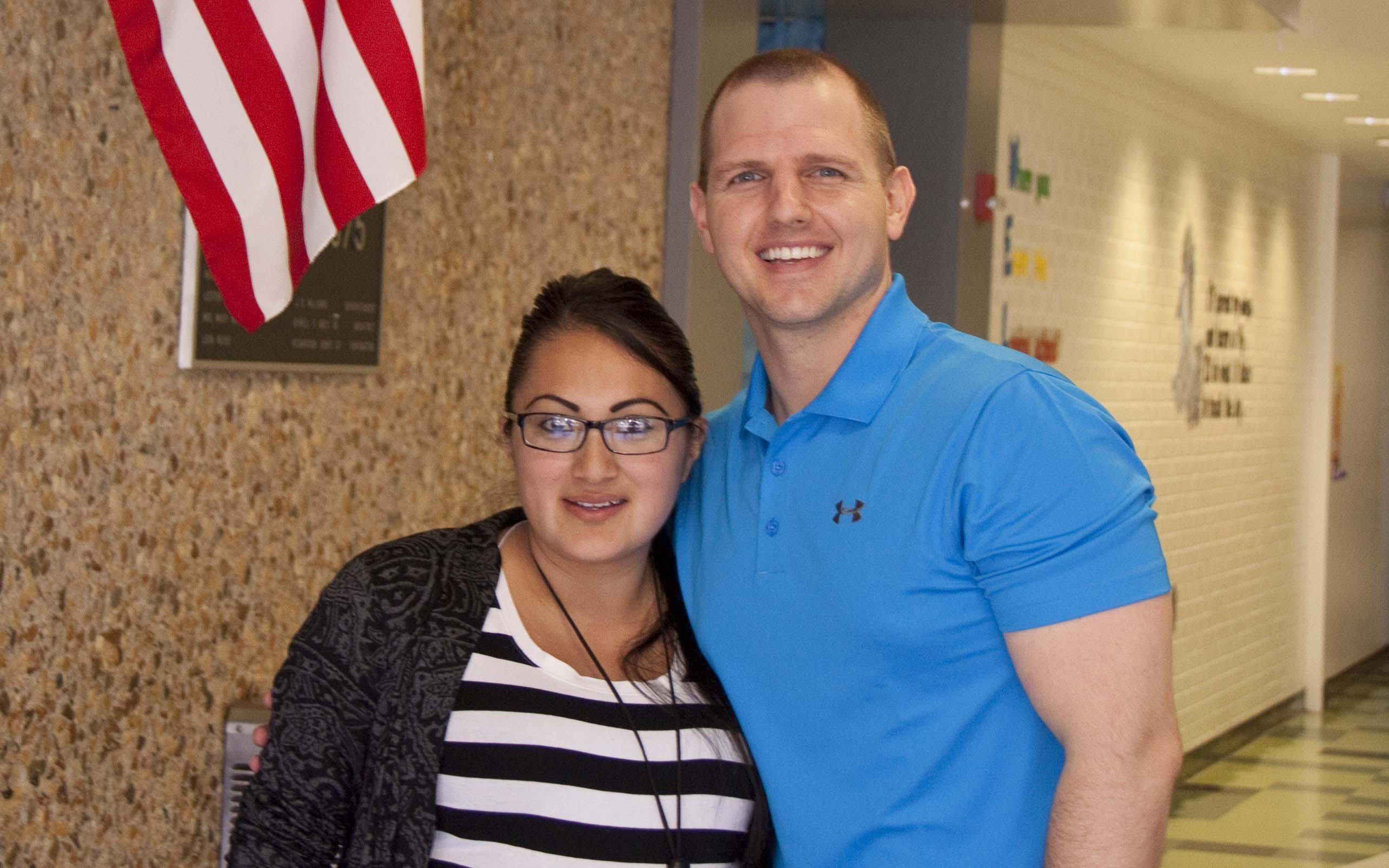 Theresa Villeda, instructional aide, stands with Jonathan Crossley in the halls of Baseline.