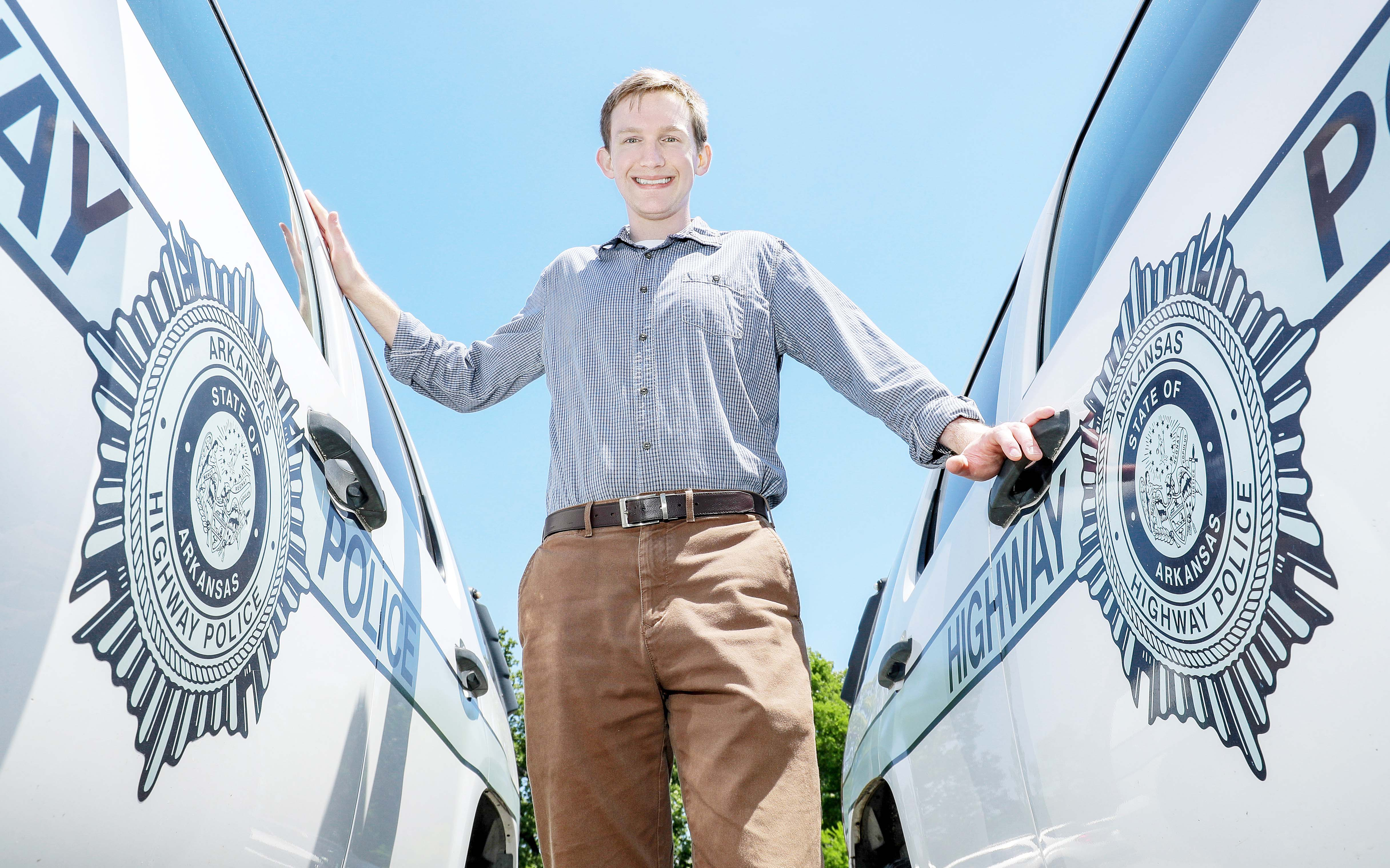 Cody Besett stands between two Arkansas Highway Patrol vehicles. (Photo by Ben Krain)